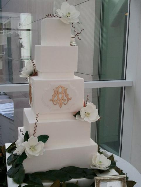 5 tier white cubic wedding cake with gold monogram on third tier and white flowers.JPG