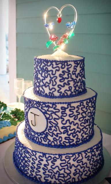3 tier round white wedding cake with blue pattern and monogram on second tier and heart loop