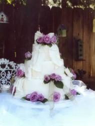 big fancy wedding cake with purple roses