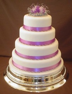 elegant wedding cake with purple ribbons and purple flowers topper