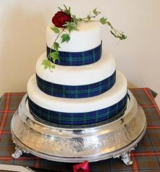 3 tier round white wedding cake with plaid blue bands and fresh rose on top.JPG