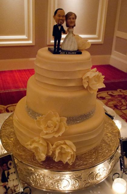 3 tier round white wedding cake with bride and groom custom bobble head toppers.JPG