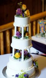 Small 4 tier round white wedding cake with Roman pillars and fresh flowers.JPG