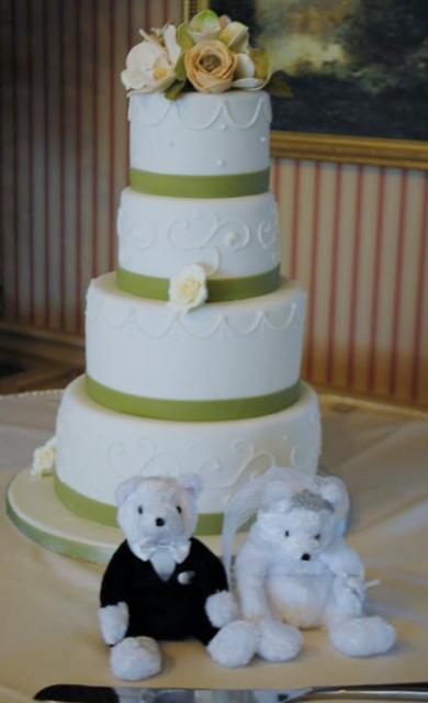 4 tier round white wedding cake with fresh flowers on top and bride and groom teddy bears.JPG