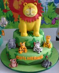 2 tier green safari theme cake with large lion on top along with other animals surrounding.JPG