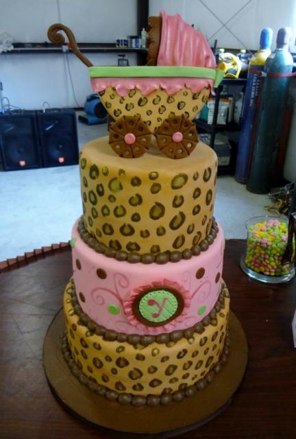 3 tier baby shower cake with leopard prints and baby stroller on top.