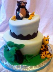 Two tier baby shower cake with teddy bear with milk bottle on top and giraffe.JPG