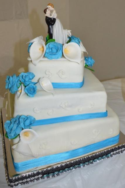 3 Tier Square White Offset Wedding Cake With Blue Band And Flowers With Topper Of Groom Holding
