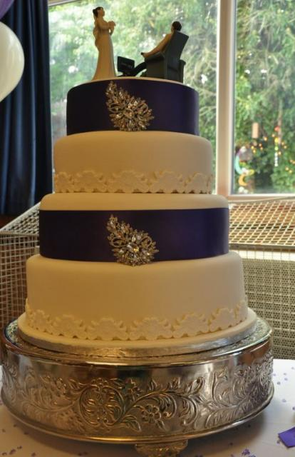 Quad tier wedding cake with black bands and bride and groom topper with groom on a chair watching TV.JPG
