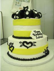 White birthday cake with yellow ribbons and black decor.jpg