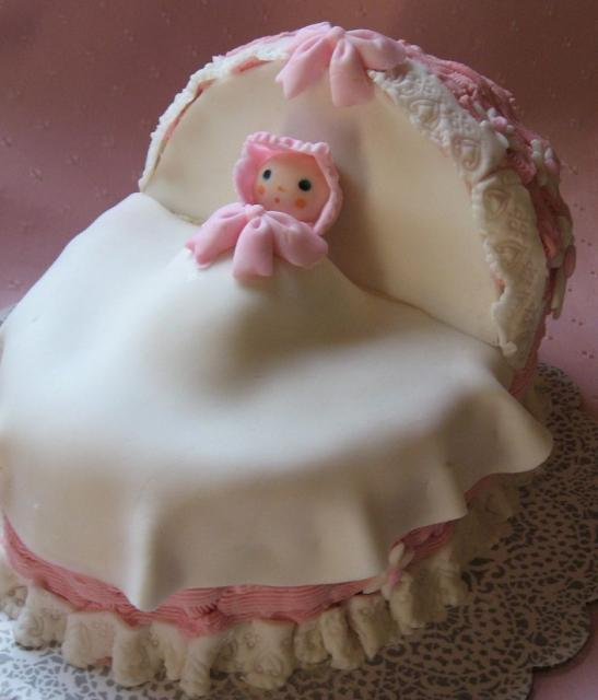 Image of lovely baby shower cake for baby girl w/ baby + basket
