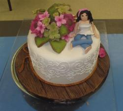 Bridal shower round white cake with fresh leaves and flowers and figurine.JPG