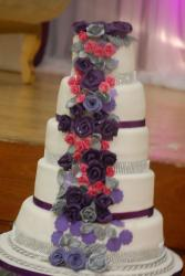 5 tier round white wedding cake with diamond bands and flowing flowers.JPG