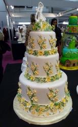 Ivory 3 Tier Wedding Cake with Yellow Flower decor & Dancing Bride Groom Topper.JPG