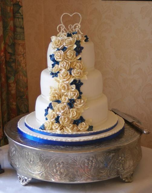 3 Tier Round White Wedding Cake With White And Blue Flowers Flowing Down And Crystal Monogram