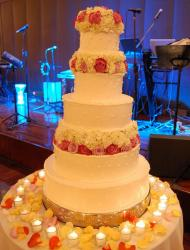 5 tier round white wedding cake with fresh flowers as toppers and in between some of the tiers.JPG