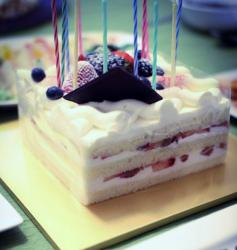 Square cut birthday cake with fresh strawberries and cream in between layers and fresh berries on top.JPG