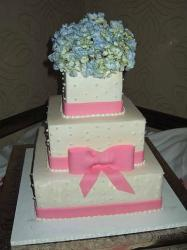 pink square wedding cake with blue flowers topper