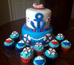 Two tier baby shower cake with anchor and ocean with baby on top and accompanying cupcakes.JPG