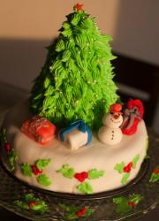 Round white small Christmas cake with tree and snowman and presents.JPG