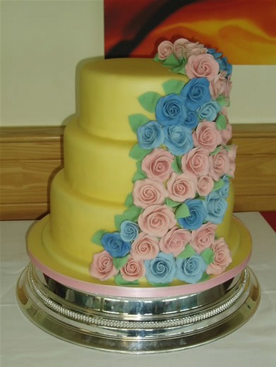 bright yellow wedding cake with blue and pink rose cascade