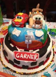 Two tier Cars birthday cake with Lightning McQueen and Mater on top.JPG