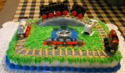 Thomas the train with real trains as cake decor and train tracks on the top.PNG