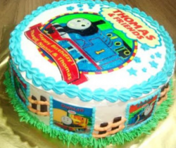 Thomas the train round cake with cake decor Thomas and other trains decorating on the sides of the cake.PNG