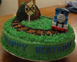 Green kids birthday cake with Thomas the train theme with Thomas the train on the train tracks_very detailed kids birthday cake.