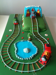 Large Thomas and friends cake with Thomas, Percy and James on the train tracks on large green grass.PNG