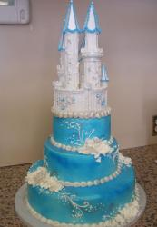 3 tier blue wedding cake with white castle on top with tall towers.JPG