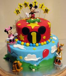 Disney theme 2 tier first birthday cake with Mickey Mouse on top along with Minnie Mouse Pluto and Annabel.JPG